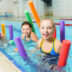 Happy and smiling group of children learning to swim with